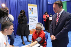 Westchester County Executive Robert P. Astorino observes a student technician take a senior's vital signs at the local launch of TIPS at the County Center on May 8.